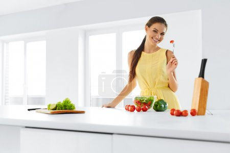 Photo for Organic Food. Portrait Of Young Smiling Woman Eating Fresh Healthy Vegetable Salad In Modern Kitchen. Healthy Eating, Meal, Lifestyle Concept. Health, Diet, Fitness. Nutrition. - Royalty Free Image