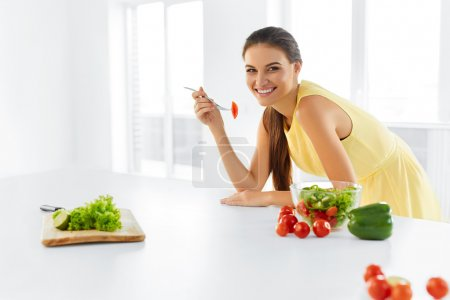 Photo for Healthy Diet. Beautiful Smiling Woman Eating Fresh Organic Vegetarian Salad In Modern Kitchen. Healthy Eating, Food And Lifestyle Concept. Health, Beauty, Dieting Concept. - Royalty Free Image