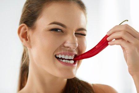 gesunde Frau, die scharfe rote Chilischote isst. Ernährung, Ernährungskonzept.