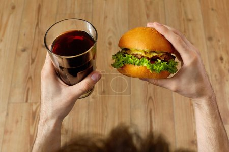 Photo for Eating Fast Food. Closeup Of Man's Hands Holding Classic American Hamburger And Glass Of Soda. Dinner At Restaurant. Point Of View. Nutrition - Royalty Free Image