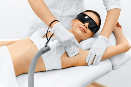 Photo for Body Care. Underarm Laser Hair Removal. Beautician Removing Hair Of Young Woman's Armpit. Laser Epilation Treatment In Cosmetic Beauty Clinic. Hairless Smooth And Soft Skin. Health And Beauty Concept. - Royalty Free Image