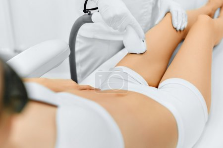 Photo for Body Care. Legs Laser Hair Removal. Beautician Removing Hair Of Young Woman's Leg. Laser Epilation Treatment In Cosmetic Beauty Clinic. Hairless Smooth And Soft Skin. Health And Beauty Concept. - Royalty Free Image