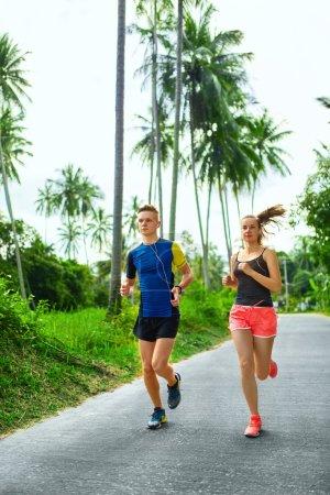 Photo pour Du sport. Couple coureur sportif courant sur le trottoir, s'entraînant pour le marathon. Femme athlétique et Fit Man jogging sur la route pendant l'entraînement en plein air. Fitness et mode de vie sain. Concept conscient de la santé - image libre de droit