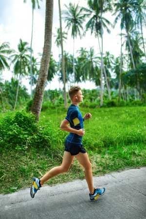 Photo for Sports. Sporty  Young Male Runner Running On Road. Jogger Training For Marathon Run. Athletic Fit Man Jogging During Workout Outside. Fitness And Healthy Lifestyle. Health Conscious Concept - Royalty Free Image