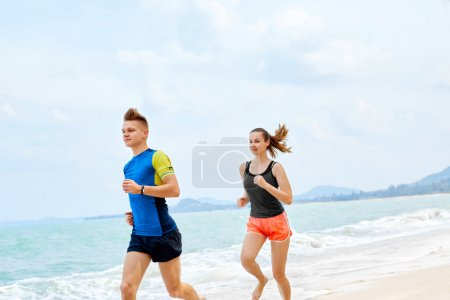 Healthy Lifestyle. Athletic Couple Running On Beach. Sports, Fit