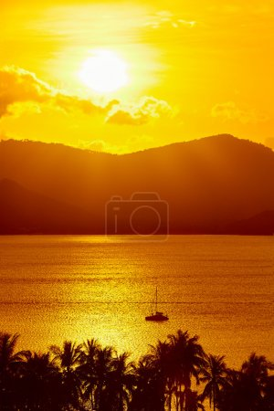 Photo pour Contexte nature. Paysage scénique de vue de côte tropicale d'île au coucher du soleil orange au-dessus de la belle mer avec le bateau flottant et la silhouette de paumes. paysage. Voyage en Thaïlande. tourisme. Vacances - image libre de droit
