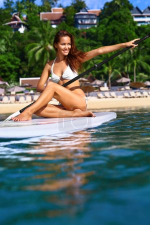 Water Sports. Healthy Woman Paddling On Surfboard. Summer Leisur