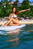 Water Sports. Healthy Woman Paddling On Surfboard. Summer Leisur