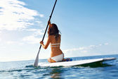 Leisure Activity. Woman Stand Up Paddling, Surfing. Recreational