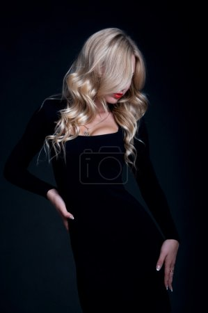 Photo pour Fashion portrait of pretty slim blond woman model with amazing figure wearing black tight cocktail dress, red lipstick, her hair made in locks, main contrast and focus on her lips. Over black background - image libre de droit