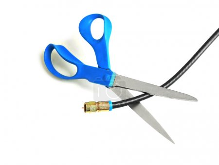 Photo pour Scissors cutting through a coaxial cable - cut the cable tv concept - image libre de droit