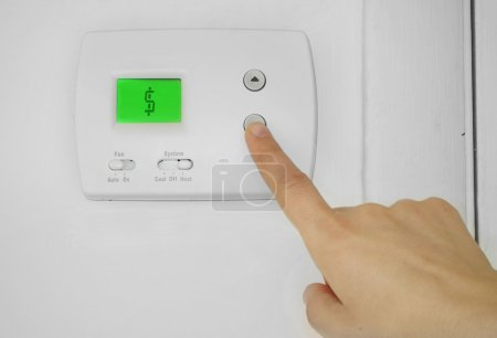 Person adjusting a wall thermostat with dollar sig...