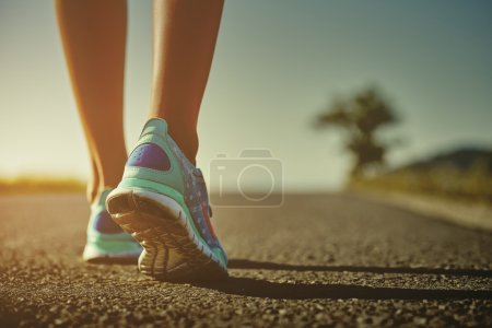 Photo for Closeup of female runner shaved feet in running shoes going for a run on the road at sunrise or sunset. Shallow depth of field, toned with instagram like filter, flare effect. - Royalty Free Image