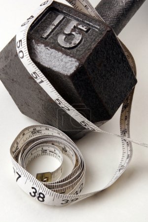 Photo for Dumbbell and measuring  tape on  white background. A healthy way of life - Royalty Free Image