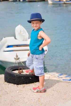 Little fishman near boat in summer