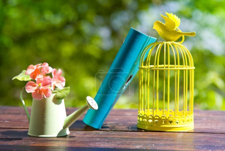 Decorative bird cage, book and flowers in can