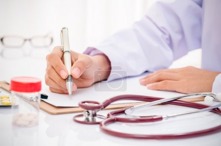 Photo for Doctor writing record on folder on desk in office - Royalty Free Image