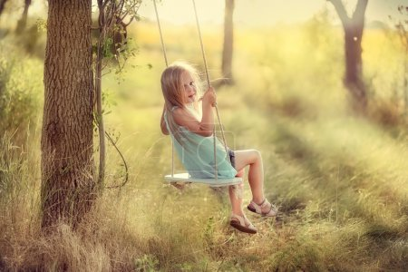 Photo for In the park near the big trees ride on a swing Pretty girl with long hair - Royalty Free Image