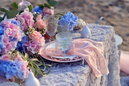 Foto de En Ramos de manteles de encaje en los floreros de hortensias azules y rosa, platos con servilletas - Imagen libre de derechos