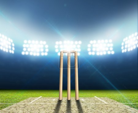 Photo for A cricket stadium with cricket pitch and set up wickets at night under illuminated floodlights - Royalty Free Image
