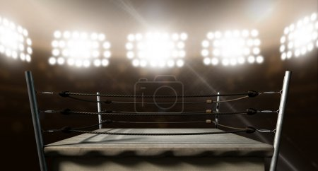 Photo for An old vintage boxing ring surrounded by ropes spotlit by floodlights in an arena setting at night - Royalty Free Image