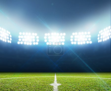Photo for A soccer stadium with a marked green grass pitch at night under illuminated floodlights - Royalty Free Image