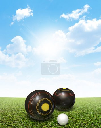 Photo for A set of wooden lawn bowls next to a jack on a perfect flat green lawn against a blue sky with white clouds - Royalty Free Image