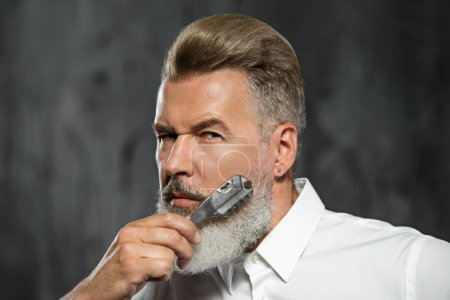 Photo for Portrait of stylish professional hairdresser with beard. Man wearing shirt, looking at camera and holding scissors near his beard - Royalty Free Image