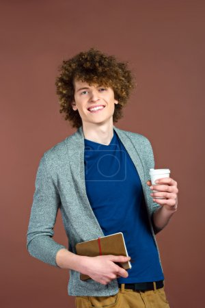 Photo for Portrait of stylish handsome young redheaded man. Man standing against brown background, holding cup of coffee to go wirh book and smiling - Royalty Free Image