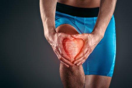 Photo pour Plan studio d'un beau jeune sportif au torse nu. Homme musculaire souffrant de douleurs au genou. Tache rouge sur le genou - image libre de droit