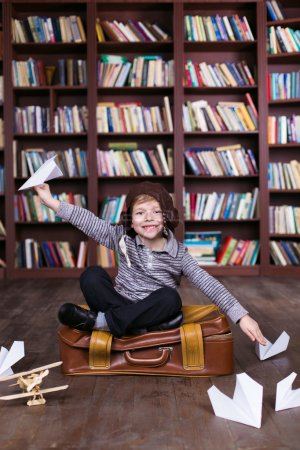 Photo for Playful childhood. Little boy having fun at room with bookshelf and sitting at suitcase. Boy pretending to be pilot - Royalty Free Image