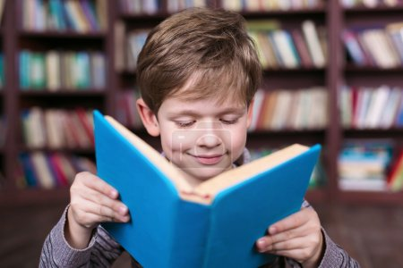 Photo for Playful childhood. Little boy having fun at room with bookshelf. Boy reading book - Royalty Free Image