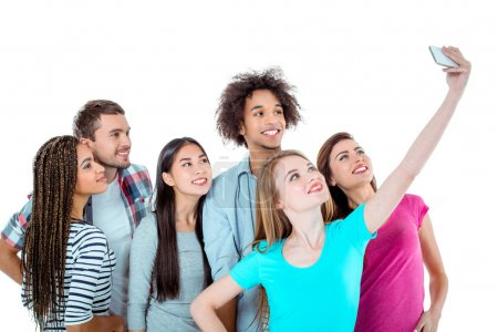 Photo for Studio shot of nice young multicultural friends. Beautiful people smiling and making selfie photo on mobile phone. Isolated background - Royalty Free Image