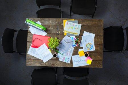 Foto de Foto creativa vista superior de mesa vintage madera oscura llena de gráficos. Objetos después de la reunión. Concepto de trabajo en equipo exitoso - Imagen libre de derechos
