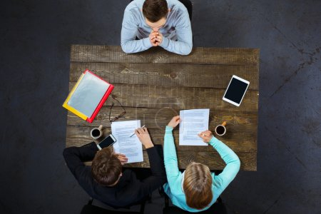 Photo for Top view creative photo of business people sitting at dark wooden vintage table. Employers having meeting. Concept for successful interview. There are electronic gadgets and documents at table - Royalty Free Image