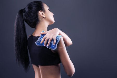 Photo for Body pain. Studio shot of beautiful young woman with dark brown hair. Woman suffering from shoulder pain. Woman holding freezing gel on shoulder - Royalty Free Image