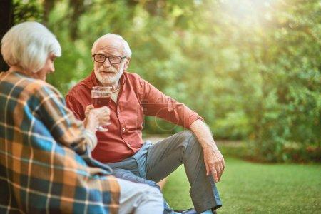 Photo pour Heureux homme âgé regardant sa femme tout en tenant des verres avec du vin rouge à l'extérieur. Relation et concept familial. Espace de copie - image libre de droit