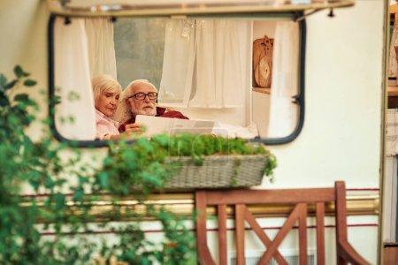 Photo pour Couple de personnes âgées regardant attentivement le nouvel itinéraire sur la carte tout en se relaxant dans leur camping-car. Concept de voyage - image libre de droit