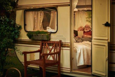 Photo pour Heureux couple marié âgé couché sur le canapé dans leur camping-car et la lecture d'un livre dans la soirée. Concept de voyage - image libre de droit
