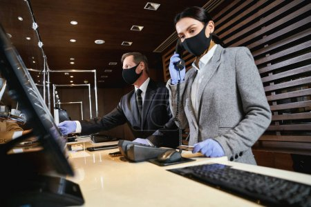 Foto de La administradora contesta llamadas telefónicas mientras que un recepcionista masculino ayuda a los visitantes. Máscaras médicas y guantes de goma en ellos - Imagen libre de derechos