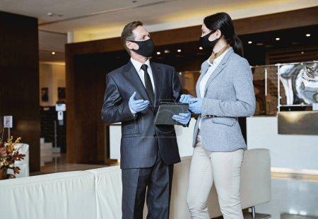 Foto de Elegante hombre y mujer con máscaras médicas y guantes de goma mirándose mientras se comunican en el vestíbulo de un hotel - Imagen libre de derechos
