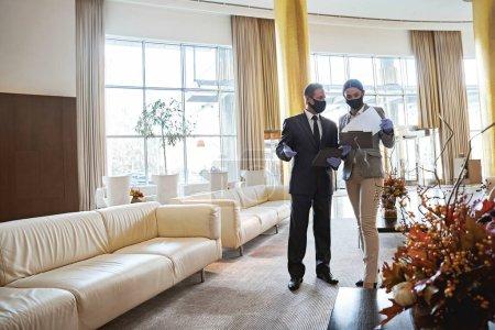 Foto de Dos administradores de pie en un hotel y una mujer revisando los documentos mientras un hombre habla con ella - Imagen libre de derechos