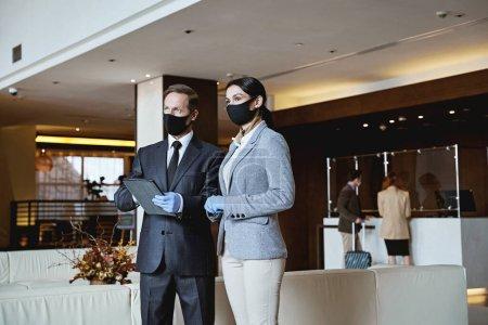 Foto de Administradores serios y atentos hombres y mujeres mirando a la distancia en el vestíbulo de un hotel - Imagen libre de derechos