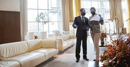 Foto de Administradores profesionales del hotel que trabajan con documentos en un amplio salón. Máscaras médicas en sus caras - Imagen libre de derechos