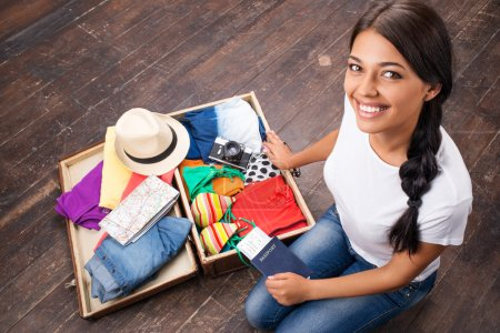 Photo for Smiling girl sitting on the floor and checking her suitcase - Royalty Free Image