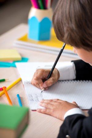 School boy writing in notebook