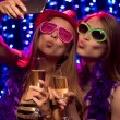 Two beautiful young women with glasses of champagne making selfie at party in night club