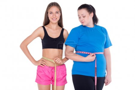 Photo for Two contradictions. Young woman with well set up figure and young overweight woman measuring, isolated on white - Royalty Free Image
