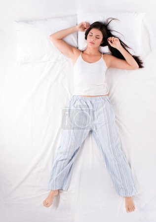 Photo pour Beautiful young woman sleeping in free fall position on white bed - image libre de droit