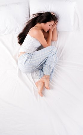 Photo pour Beautiful young woman sleeping in fetal position on white bed - image libre de droit